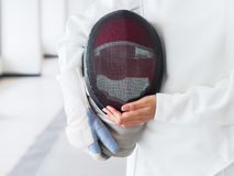 Close-up of a fencer in white fencing suit and holding mask on g royalty free stock images