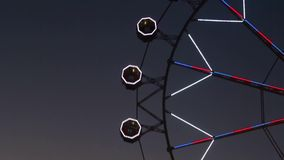 Close-up of Ferris wheel by rotating at night. Close-up of Ferris wheel by rotating at night with large colorful of led lights and motion. Normal speed stock footage