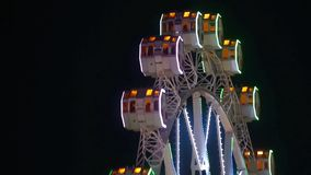 Close-up of Ferris wheel by rotating at night. Close-up of Ferris wheel by rotating at night with large colorful of led lights and motion. Normal speed stock video footage