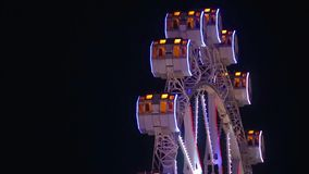 Close-up of Ferris wheel by rotating at night. Close-up of Ferris wheel by rotating at night with large colorful of led lights and motion.Slow backward turns stock footage