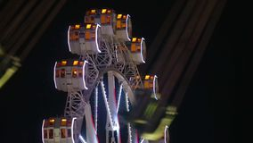 Close-up of Ferris wheel and unfocused carousel by rotating at night. Close-up of Ferris wheel and unfocused carousel that crosses in front, by rotating at stock video