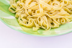 Close up of fettuccine pasta and olive oil in green plate isolat Royalty Free Stock Images