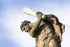 Close-up of the fighter statue holding club looking down with blue sky in background Royalty Free Stock Images