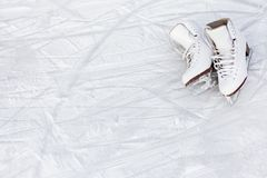 Close up of figure skates and copy space over ice background with marks from skating. Close up of white figure skates and copy space over ice background with royalty free stock photo