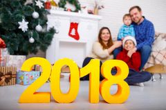 Close-up of the figures of 2018, in the background a happy family at home Royalty Free Stock Images
