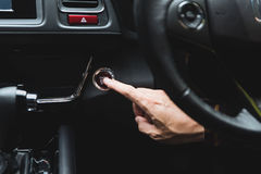 Close up Finger press button functions car engine start and stop Stock Photos