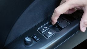 Close-up of finger pressing button controlling and adjustments window in car. Technology and transportation concepts.