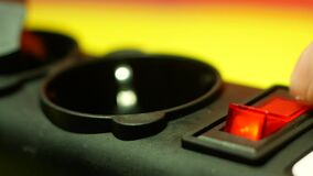 Close-up of a finger turns on the red button of an electrical appliance. Red button for 220 volt power filter. Selective focus, sh