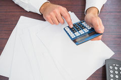 Close up of finger using calculator at desk Stock Image