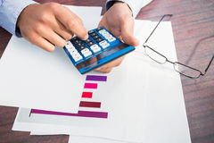 Close up of finger using calculator at desk. In a large warehouse Royalty Free Stock Photo