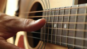 Close up. The fingers of the musician to touch the strings of the guitar. A man plays an acoustic guitar. Music and. Hobbies. 4K stock video footage