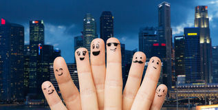 Close up of fingers with smiley faces over city Stock Images