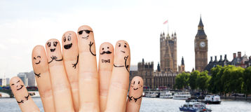 Close up of fingers with smiley faces over london Royalty Free Stock Photos