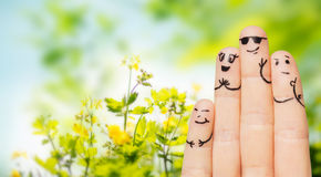 Close up of fingers with smiley faces over nature Royalty Free Stock Photo