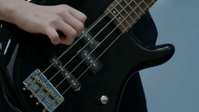Close-up of the fingers of a teenager playing a black electric bass guitar. The guy pulled the strings on a musical stock video