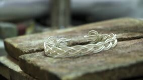 Close-up of a finished silver bracelet on a jeweler`s desktop, manual production of silver jewelry, selective focus