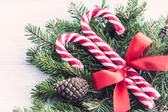 Close up of a fir tree and candy cones tied with a red bow over an old white wood background. Christmas decoration background. Royalty Free Stock Photo
