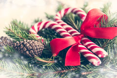 Close up of a fir tree and candy cones tied with a red bow over an old white wood background. Christmas decoration background. Vin Stock Photography