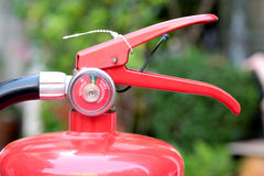 Close- up Fire extinguisher red tank with green background. Royalty Free Stock Image