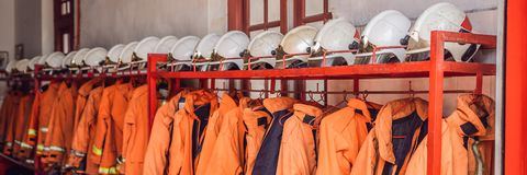 Close up of Fireman coats, helmets and boots wait for the next call. Dressing room of the volunteer fire department. BANNER long format royalty free stock photo