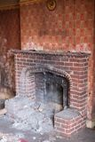 Close up of fireplace in derelict house, with wallpaper peeling off the wall. Rayners Lane, Harrow UK royalty free stock photography