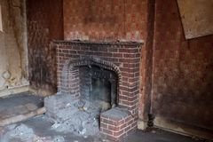 Close up of fireplace in derelict house, with wallpaper peeling off the wall. Harrow UK royalty free stock photo