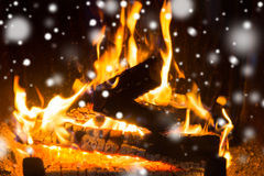 Close up of firewood burning in fireplace and snow. Winter, christmas, warmth, fire and coziness concept - close up of firewood burning in fireplace with snow Stock Images
