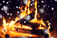 Close up of firewood burning in fireplace and snow. Winter, christmas, warmth, fire and coziness concept - close up of firewood burning in fireplace with snow Royalty Free Stock Photo