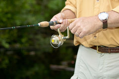 Close up of fisherman using fishing reel. A close up of a well dressed fisherman using a fishing reel as he retrieves a lure on light tackle Royalty Free Stock Images