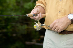 Close up of fisherman winding fishing reel. A close up of a well dressed fisherman winding a fishing reel as he retrieves a lure on light tackle Stock Photography