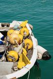 Close up of a fishing boat in the harbor. Close up of a small fishing boat with fishing equipment buoys for the nets docked in the port - Liguria, Italy Stock Photography