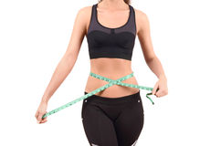 Close up on fit girl abdomen with green measuring tape around the waist. Royalty Free Stock Images