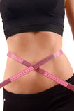 Close up on fit girl abdomen with pink measuring tape around the waist. Stock Image