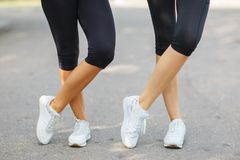 Close-up fit legs in sportswear on a blurred background. Girls in sneakers. Runner concept. Close-up of legs in black leggings and comfortable sports sneakers Stock Photo