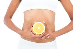 Close up of a fit model keeping half an orange Royalty Free Stock Photo