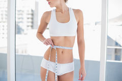 Close up of a fit woman measuring her waist Royalty Free Stock Photos