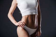 Close up of fit woman's torso with her hands on hips. Female with perfect abdomen muscles on black background Royalty Free Stock Images