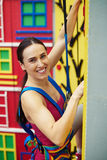 Close-up of fit woman in safety harness on the rock-climbing wal Stock Images