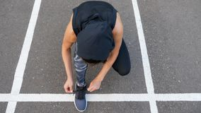 Close up of fit woman tying shoelaces while standing on asphalt road during jog in summer evening royalty free stock image