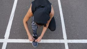 Close up of fit woman tying shoelaces while standing on asphalt road during jog in summer evening