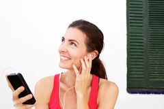 Close up fit young woman relaxing with mobile phone and earphones after workout session. Close up portrait of fit young woman relaxing with mobile phone and Royalty Free Stock Photos