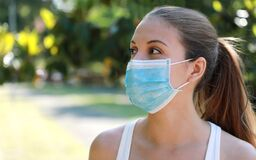 Free Close Up Fitness Girl Wearing Surgical Mask In The Park Looking To The Side. Portrait Of Young Sporty Woman With Protective Mask Royalty Free Stock Photo - 184201585