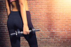 Close up of a Fitness woman with a dumbbell in the gym with brick wall copy space in background .fitness and healthy lifestyle stock photos