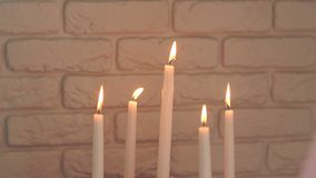 Five burning candles against the brick wall. Close-up of five burning candles in candlesticks against a white brick wall. Candelabrum with 5 white candle sticks