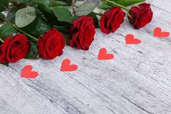 Close-up of five red roses paralyzed paper hearts, holiday concept. Stock Image