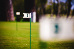 Close up of flag mark in hole on golf field Stock Photos