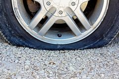 Close up on Flat Car Tire on Gravel Road Stock Image