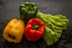 Close up. Flat lay. Three sweet peppers paprika and a bunch of green lettuce on black background royalty free stock images
