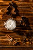 Close up, flat lay. A white candle in a glass candlestick, cinnamon, anise, metal molds are laid out around it. stock photo