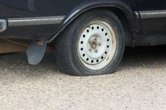 Close up Flat tire and old car on the road waiting for repair. stock image